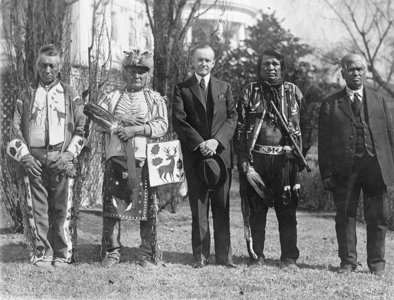 Calvin Coolidge, 30e président des Etats-Unis (2 août 1923 – 4 mars 1929) avec des membres de la tribu des Osages lors de la signature de l'Indian Citizenship Act, National Photo Company, Library of Congress, 1924.