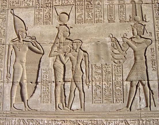 La déesse Hathor donnant le sein à son fils Ihy, Mammisi (temple de la naissance) de Denderah, époque ptolémaïque et romaine, Egypte. Le pharaon offre un collier à Hathor. Derrière la déesse, Ihy est représenté une seconde fois, plus grand.