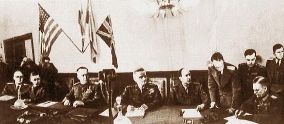 Keitel ratifie l'acte de capitulation à Berlin, le 8 mai 1945, à 23h ; sous les quatre drapeaux, Joukov ; à sa gauche, Tedder, à sa droite, Spaatz et De Lattre de Tassigny. (DR)