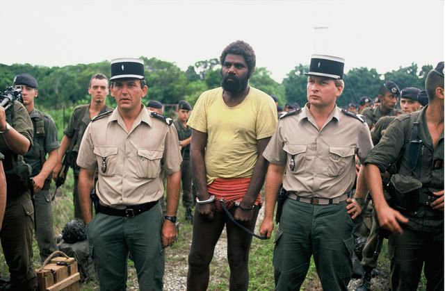 Gendarmes et prisonniers après l'assaut de la grotte d'Ouvéa (Nouvelle-Calédonie), le 5 mai 1988 (DR)