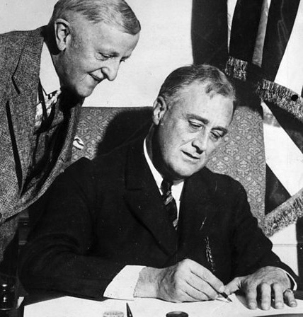 Franklin Roosevelt signe l'Emergency Banking Act (10 mars 1933) sous le regard de son Secrétaire d'État au Trésor William Woodwin (DR)
