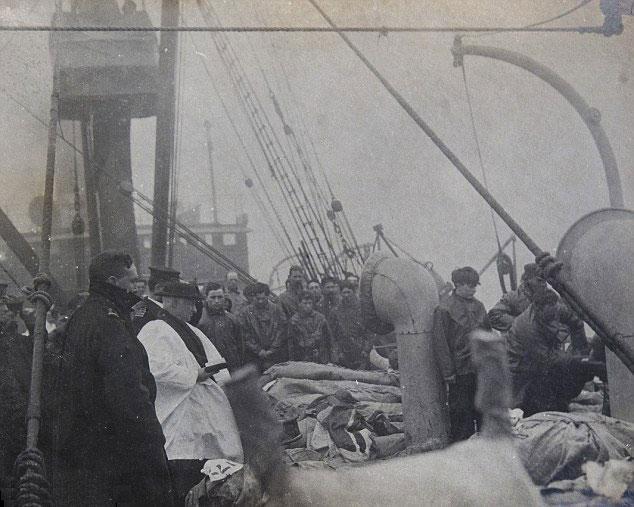Sur le pont du Carpathia, le révérend Hind prie pour les premières victimes avant leur immersion (DR)